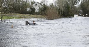 Up to his neck: Brian Keogh in the floodwater by his house, in Ballycar; the flooded sections are up to 350m long. Photograph: Liam Burke/Press 22