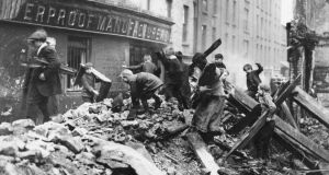 Easter 1916: children search for firewood among ruined Dublin buildings. Photograph: Central Press/Getty