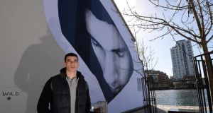 Jordan photographed standing in front of a mural of himself by Joe Caslin on the gable wall of a house in Grand Canal Dock. Photograph: Brenda Fitzsimons