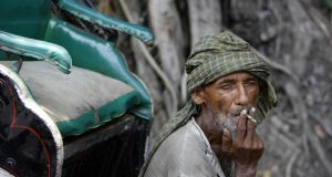 An  Indian rickshaw-driver smoking a 'bidi' cigarette in Kolkata before India's  ban on smoking in public spaces came into effect, in October2008. Photograph:  Deshakalyan Chowdhury/AFP/Getty Images