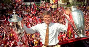 Arsenal manager Arsene Wenger posing with the FA and League Cups the club won in 1998. Photo:  John Stillwell/PA