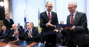 Ukrainian prime minister Arseniy Yatsenyuk (second from right) and EU Council president Herman Van Rompuy (right) exchange documents during the signing ceremony of political provisions of the Association Agreement with Ukraine at the second day of spring European head of states summit at the EU council headquaters in Brussels, yesterday. Photograph: EPA/Olivier Hoslet