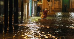 A woman walks through flood water in Cork city last month. Photograph: Niall Carson/PA Wire