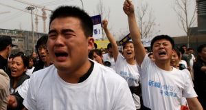 Family members of passengers onboard Malaysia Airlines MH370 cry as they shout slogans during a protest in front of the Malaysian embassy in Beijing today. Photograph: Reuters
