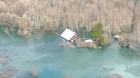 A house is isolated by the floodwaters. Photograph: Gov Jay Inslee's office/Reuters