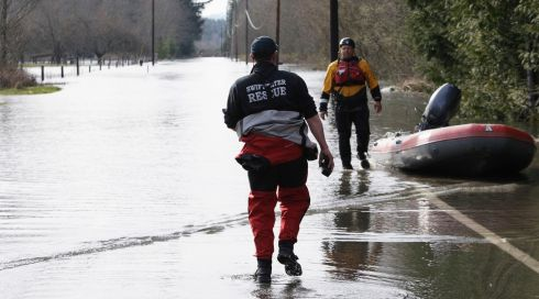Search and rescue workers on a flooded portion of Highway 530. Photograph: Jason Redmond/Reuters