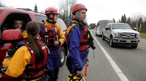 Members of a swift water rescue team prepare to deploy. Photograph: Jason Redmond/Reuters