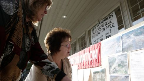 Carol Massingale (right) and Terri Englebretson look at aerial photos of the massive landslide posted outside a market in Darrington, Washington. Photograph: Jason Redmond/Reuters