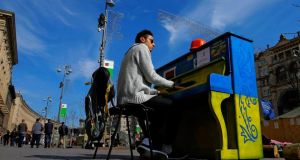 A Ukrainian student plays a piano painted in Ukraine's national colours in front of city hall near  Independence Square in Kiev yesterday.  Photograph: Robert Ghement/EPA