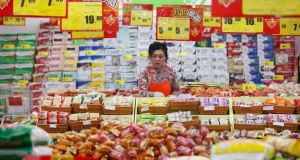 An employee arranges stock under price tags at a supermarket in Huaibei, Anhui province. Photograph: Reuters