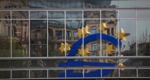 A euro sign sculpture  reflected in office windows as it stands outside the headquarters of the European Central Bank in Frankfurt. Photograph: Krisztian Bocsi/Bloomberg