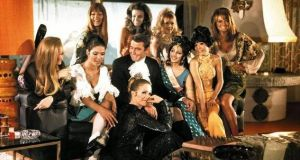 George Lazenby during filming of On Her Majesty's Secret Service with actresses including Joanna Lumley, seated in front