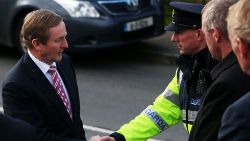 Taoiseach Enda Kenny shakes hands with a garda as he arrives for the funeral Mass of Fine Gael TD Nicky McFadden. Photograph: Brian Lawless/PA Wire