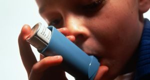 A young boy (6-8) uses an asthma inhaler