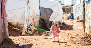 Refugees: a young girl walks through the tent settlement in Bekaa. Photograph: Naoise Culhane