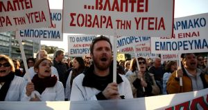 "Pharmacists at an anti-government rally outside the parliament in Athens. The main sign reads: ""The recipe of the government seriously damages health"". Photograph: Reuters/Yorgos Karahalis"