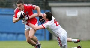 Colm Cavanagh of Tyrone tackles Cork's John O'Rourke in yesterday's close-fought game. Ryan Byrne/Inpho