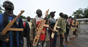 Members of the ex-Seleka rebels pose with wooden weapons in front of late Centrafrican emperor Jean-Bedel Bokassa's palace in Beringo last month. Photograph: Getty Images