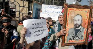 Palestinians hold placards during a protest demanding US secretary of state John Kerry  work for the release of Palestinian prisoners in Israeli jails at Balata refugee camp near the West Bank city of Nablus yesterday. Photograph: Alaa Badarneh/EPA