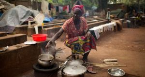 Kapiri Agnes (53) prepares a meal on the grounds of a church that is sheltering about 4,000 internally displaced people fleeing sectarian violence in Bangui. Central Africans say Christians and Muslims lived in harmony until last year. Photograph: Siegfried Modola/Reuters