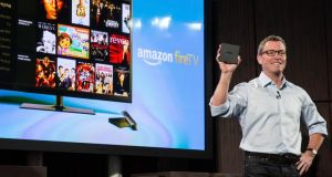 Amazon's vice president of Kindle, Peter Larsen, displays the Amazon Fire TV, a new device that allows users to stream video, music, photos, games, through their television. Photograph: Getty