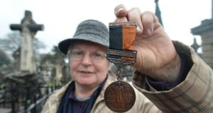 Mary Deegan Kavanagh with a medal belonging to her aunt Maire Deegan, a member of Cumann na mBan, at the ceremony to mark the centenary of the foundation of Cumann na mBan at Glasnevin Cemetery yesterday. Photograph: Alan Betson