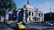 Volkswagon Beetles, still produced in Mexico, cruise by Palacio de Bellas Artes. Photograph: Getty
