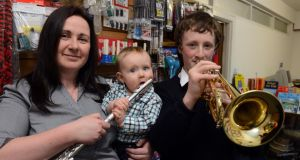 Sarah Dowdall with her sons, Eddie and Luke (13), in the family premises, woodwind and brass specialists educational music services, at Mountjoy Square. Photograph: Cyril Byrne