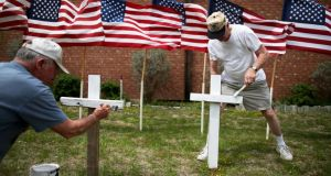 Bob Gordon (left) and Bob Butler paint crosses they placed in front of 16 American flags as they build a memorial in front of Central Christian Disciples of Christ church for the victims of the shooting at Fort Hood on April 3rd, 2014 in Killeen, Texas. Photograph: Joe Raedle/Getty Images