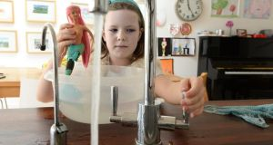 Bath time: Grace Robbins keeps an eye on how much water she is using to wash  her mermaid. Photograph: Cyril Byrne
