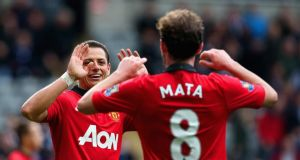 Juan Mata of Manchester United congratulates Javier Hernandez  after he scored the third goal against Newcastle. Photo: Jan Kruger/Getty Images