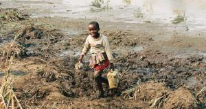 Five-year-old Neeja carries pooled dirty water back to her family's camp three kilometres away. June 1994, Rwanda. Photograph: Liam Burke/Press 22/Concern