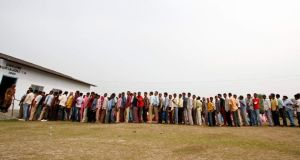 People line up to cast their vote outside a polling station at Dhekiajuli in Sonitpur district in the northeastern Indian state of Assam today. Photograph: Reuters