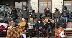 Pro-Russian protesters and their supporters sit next to a barricade erected in front of the seized regional government building in Donetsk. Photograph:  Stringer /Reuters