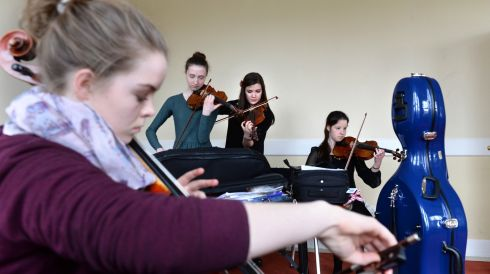 Zoe Nagle, Douglas, Cork on cello, with, from left: Eva Barry, Tullamore; Mollie Wrafters, Tullamore and Jessica O'Shea, Cork (all violin), preparing for the St Cecilia Cup Junior String competition at the Feis Ceoil.  Photograph: Dara Mac Dónaill/The Irish Times