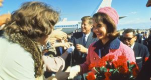 Jackie Kennedy in her famous pink suit, with JFK looking on, on the day of his assassination. Photograph: Getty