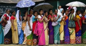 Voters wait  at a polling station during the first phase of the Indian general election in Lakhimpur district, Assam state, on Monday. Photograph: EPA