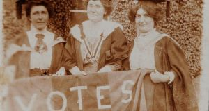 "Hanna Sheehy-Skeffington, Kathleen Shannon and Kate Sheedy, in their graduation robes and mortar-boards, carry a banner saying ""Votes"" [for women]"