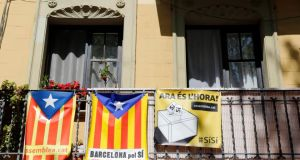 Catalan separatist flags seen hung beside a banner from a balcony in Barcelona yesterday. REUTERS/Albert Gea