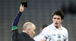Referee Marty Duffy shows David Hyland of Kildare a black card. Photo: Cathal Noonan/Inpho