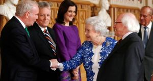 Queen Elizabeth II greets Northern Ireland's Deputy First Minister Martin McGuinness (left), First Minister Peter Robinson (2nd left) and Secretary of State for Northern Ireland Theresa Villiers (3rd left) as  President Michael D Higgins (3rd right), the Duke of Edinburgh (2nd right) and Sabina Coyne (right) look on during a Northern Ireland-themed reception at Windsor Castle today. Photograph: Luke MacGregor/PA Wire