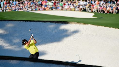Bubba Watson of the United States hits a shot from a fairway bunker on the 18th hole. Photograph: Harry How/Getty Images