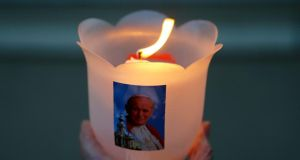 Faithful: a John Paul II candle burns in the late pope's birthplace, in Poland. Photograph: Kacper Pempel/Reuters