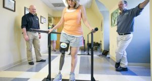 Roseann Sdoia  walking with the assistance of parallel bars   as she  tries out a new   leg  at a prosthetics clinic two months after the explosions. Photograph:  Yoon S Byun/the Boston Globe via Getty Images