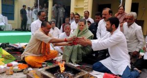 "Congress Party president Sonia Gandhi (centre) and her son, party vice-president Rahul Gandhi (right), perform a Hindu ""yagna"" ritual before she files her nominations papers for the Indian elections. Photograph: EPA"