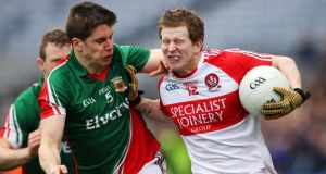 Derry's Enda Lynn holds off  Lee Keegan of Mayo. Photograph: Cathal Noonan/Inpho