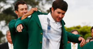 Defending Masters Champion Adam Scott of Australia helps Bubba Watson of the US (right) into his second green jacket after winning the  Masters in Augusta. Photograph: EPA