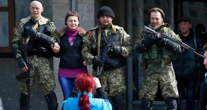 A local resident  poses for a picture with pro-Russian armed men standing guard outside the mayor's office in Slaviansk April 14th, 2014. Photograph:  Gleb Garanich/Reuters.
