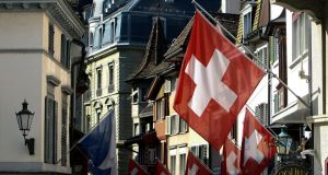 Swiss national flags hang from buildings in a shopping district in Zurich. Photographer: Chris Ratcliffe/Bloomberg
