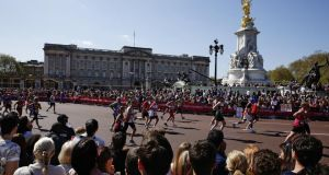 Huge crowds watch the runners as they pass Buckingham Palace during the Virgin London Marathon. Photograph: Miles Willis/Getty Images
